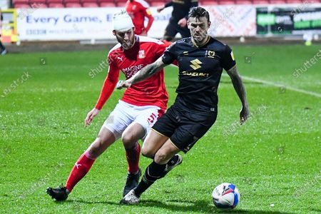 Swindon Town defender Jonathan Grounds (5) wearing a white bandage on his head tackles Milton Keynes Dons midfielder Ben Gladwin (7) during the EFL Sky Bet League 1 match between Swindon Town and Milton Keynes Dons at the County Ground, Swindon