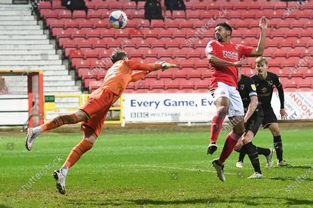 Milton Keynes Dons goalkeeper (on loan from Blackburn Rovers) Andrew Fisher (13)makes an important save from Swindon Town defender Zeki Fryers (3) header during the EFL Sky Bet League 1 match between Swindon Town and Milton Keynes Dons at the County Ground, Swindon