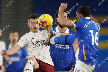 Brighton's Alireza Jahanbakhsh, right, challenges for the ball with Arsenal's Granit Xhaka during the English Premier League soccer match between Brighton and Arsenal at the Falmer stadium in Brighton, England