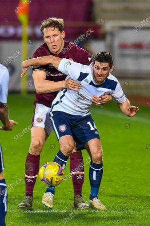 Kris Doolan (#14) of Arbroath FC holds off Christophe Berra (#6) of Heart of Midlothian FC during the SPFL Championship match between Heart of Midlothian and Arbroath at Tynecastle Park, Edinburgh