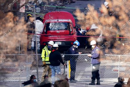 Car is inspected at the site of a Christmas Day explosion, in Nashville, Tenn. Officials have named 63-year-old Anthony Quinn Warner as the man behind the bombing in which he was killed, but his motive remains elusive