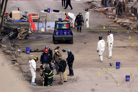 And ATF personnel examine the area involved in a Christmas Day explosion, in Nashville, Tenn. Officials have named 63-year-old Anthony Quinn Warner as the man behind the bombing in which he was killed, but the motive has remained elusive