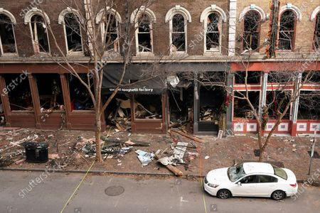 Debris remains on the sidewalk in front of buildings damaged in a Christmas Day explosion, in Nashville, Tenn. Officials have named 63-year-old Anthony Quinn Warner as the man behind the bombing in which he was killed, but the motive has remained elusive