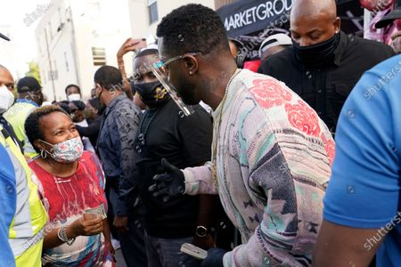 """Rapper Sean """"Diddy"""" Combs, right, passes out fifty dollar bills to residents in the Overtown neighborhood of Miami, . Various organizations came together to also pass out gift cards and gift bags with essentials to those in need during the coronavirus pandemic"""