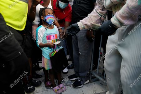 """Girl accepts a fifty dollar bill handed out by rapper Sean """"Diddy"""" Combs as he passes out the bills to residents in the Overtown neighborhood of Miami, . Various organizations came together to also pass out gift cards and gift bags with essentials to those in need during the coronavirus pandemic"""
