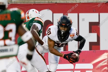 Stock Picture of Oklahoma State wide receiver Brennan Presley (80) makes a reception for a touchdown in against Miami linebacker Keontra Smith during the first half of the Cheez-it Bowl NCAA college football game, in Orlando, Fla
