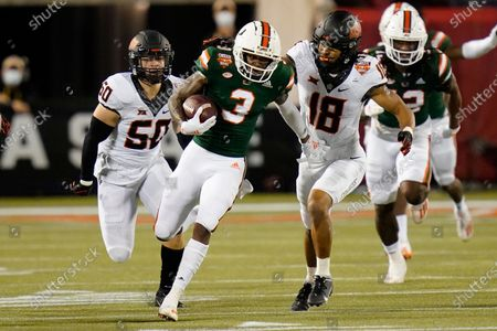 Miami wide receiver Mike Harley, center, runs for yardage past Oklahoma State linebacker Relijah Sherman (50) and safety Sean Michael Flanagan (18) during the first half of the Cheez-it Bowl NCAA college football game, in Orlando, Fla