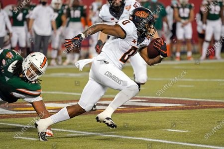 Stock Image of Oklahoma State running back LD Brown (0) gains yardage against Miami during the second half of the Cheez-it Bowl NCAA college football game, in Orlando, Fla