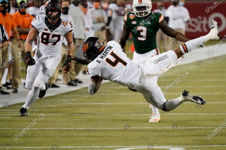 Oklahoma State wide receiver Tay Martin (4) makes a reception in front of Miami linebacker Gilbert Frierson (3) during the second half of the Cheez-it Bowl NCAA college football game, in Orlando, Fla