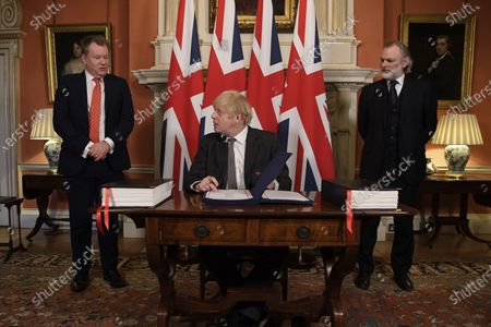 Stock Picture of UK chief trade negotiator David Frost, left, and British Ambassador to the EU Tim Barrow, right, look on as Britain's Prime Minister Boris Johnson signs the EU-UK Trade and Cooperation Agreement at 10 Downing Street, London . The U.K. left the EU almost a year ago, but remained within the bloc's economic embrace during a transition period that ends at midnight Brussels time -- 11 p.m. in London - on Thursday. European Commission President Ursula von der Leyen and European Council President Charles Michel signed the agreement during a brief ceremony in Brussels on Wednesday morning then the documents were flown by Royal Air Force plane to London for Johnson to add his signature