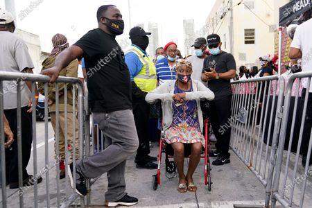 """Residents in the Overtown neighborhood of Miami wait in line to receive gift cards and gift bags with essentials, . Various organizations came together to distribute items to those in need during the coronavirus pandemic. Rapper Sean """"Diddy"""" Combs also passed out fifty dollar bills to residents"""