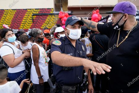 """City of Miami police officer controls the crowd as residents in the Overtown neighborhood of Miami wait in line to receive gift cards and gift bags with essentials, . Various organizations came together to distribute items to those in need during the coronavirus pandemic. Rapper Sean """"Diddy"""" Combs also passed out fifty dollar bills to residents"""