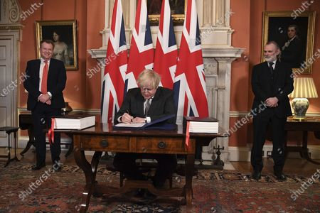 UK chief trade negotiator David Frost, left, and British Ambassador to the EU Tim Barrow, right, look on as Britain's Prime Minister Boris Johnson signs the EU-UK Trade and Cooperation Agreement at 10 Downing Street, London . The U.K. left the EU almost a year ago, but remained within the bloc's economic embrace during a transition period that ends at midnight Brussels time -- 11 p.m. in London - on Thursday. European Commission President Ursula von der Leyen and European Council President Charles Michel signed the agreement during a brief ceremony in Brussels on Wednesday morning then the documents were flown by Royal Air Force plane to London for Johnson to add his signature