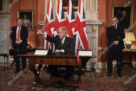 Stock Photo of UK chief trade negotiator David Frost, left, and British Ambassador to the EU Tim Barrow, right, look on as Britain's Prime Minister Boris Johnson signs the EU-UK Trade and Cooperation Agreement at 10 Downing Street, London . The U.K. left the EU almost a year ago, but remained within the bloc's economic embrace during a transition period that ends at midnight Brussels time -- 11 p.m. in London - on Thursday. European Commission President Ursula von der Leyen and European Council President Charles Michel signed the agreement during a brief ceremony in Brussels on Wednesday morning then the documents were flown by Royal Air Force plane to London for Johnson to add his signature