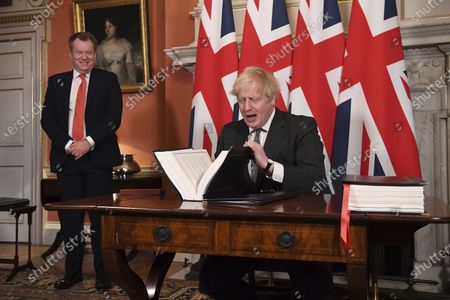 UK chief trade negotiator David Frost looks on as Britain's Prime Minister Boris Johnson signs the EU-UK Trade and Cooperation Agreement at 10 Downing Street, London . The U.K. left the EU almost a year ago, but remained within the bloc's economic embrace during a transition period that ends at midnight Brussels time -- 11 p.m. in London - on Thursday. European Commission President Ursula von der Leyen and European Council President Charles Michel signed the agreement during a brief ceremony in Brussels on Wednesday morning then the documents were flown by Royal Air Force plane to London for Johnson to add his signature