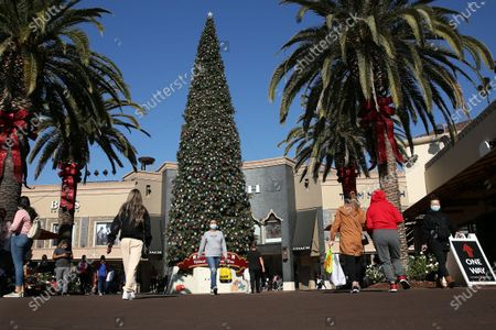 Shoppers enter and exit the Citadel Outlets in Commerce on Tuesday, Dec. 22, 2020 in Los Angeles, CA. The center was heavily trafficked despite the Calvin Klein store at Citadel Outlets reported an outbreak after 3 employees got with and a general Covid-19 surge within L.A. Country. (Dania Maxwell / Los Angeles Times)