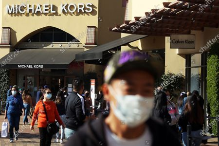 Shoppers wear protectice facial coverings at the Citadel Outlets in Commerce on Tuesday, Dec. 22, 2020 in Los Angeles, CA. The center was heavily trafficked despite the Calvin Klein store at Citadel Outlets reported an outbreak after 3 employees got with and a general Covid-19 surge within L.A. Country. (Dania Maxwell / Los Angeles Times)