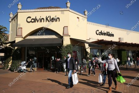 Shoppers wait in line to enter the Calvin Klein store at the Citadel Outlets in Commerce on Tuesday, Dec. 22, 2020 in Los Angeles, CA. The center was heavily trafficked despite the Calvin Klein store reported an outbreak after 3 employees got with and a general Covid-19 surge within L.A. Country. (Dania Maxwell / Los Angeles Times)