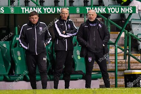 Stock Photo of (LtoR) Richard Brittain, assistant manager of of Ross County FC, Scott Thomson, goalkeeping coach of Ross County FC and John Hughes, manager of Ross County FC during the SPFL Premiership match between Hibernian and Ross County at Easter Road Stadium, Edinburgh