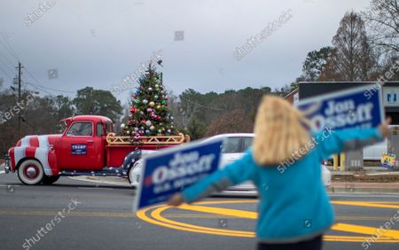 A bird tries to land on the Christmas tree of a President Donald J. Trump supporter as he drives by a Latino outreach rally for Democratic Georgia US Senate candidate Jon Ossoff in Marietta, Georgia, USA, 30 December 2020. Ossoff is running against Republican Senator David Perdue in a 05 January 2021 runoff election.
