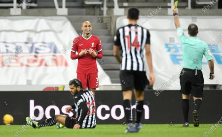 Liverpool's Fabinho, second left is shown a yellow card by referee paul Tinery, right, for a foul on Newcastle's DeAndre Yedlin, left, during the English Premier League soccer match between Newcastle United and Liverpool at St James' Park stadium in Newcastle, England