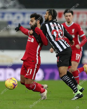 Liverpool's Mohamed Salah, left vies for the ball with Newcastle's DeAndre Yedlin during the English Premier League soccer match between Newcastle United and Liverpool at St James' Park stadium in Newcastle, England