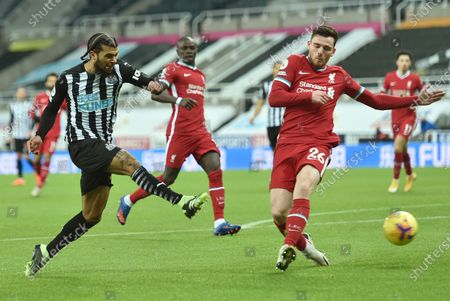Newcastle's DeAndre Yedlin, left takes a shot on goal under pressure from Liverpool's Andrew Robertson during the English Premier League soccer match between Newcastle United and Liverpool at St James' Park stadium in Newcastle, England
