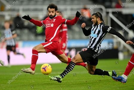 Newcastle's DeAndre Yedlin, right, challenges Liverpool's Mohamed Salah during the English Premier League soccer match between Newcastle United and Liverpool at St James' Park stadium in Newcastle, England