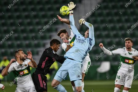 Real Madrid's goalkeeper Thibaut Courtois and Elche's Lucas Boye, center, jump for the ball during the Spanish La Liga soccer match between Real Madrid and Elche CF at the Manuel Martinez Valero stadium in Elche, Spain