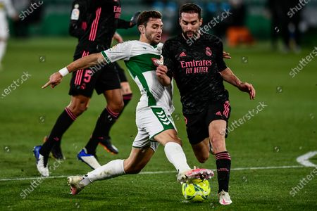 Elche's Lucas Boye, left, duels for the ball with Real Madrid's Dani Carvajal during the Spanish La Liga soccer match between Real Madrid and Elche CF at the Manuel Martinez Valero stadium in Elche, Spain