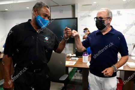 Former Miami Dolphins football player Nat Moore, 69, left, bumps fists with music producer Emilio Estefan, 67, right, before receiving the Pfizer-BioNTech COVID-19 vaccine at Jackson Memorial Hospital, in Miami. Jackson Health System is starting to vaccinate people over the age of 65 this week