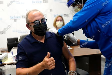 Music producer Emilio Estefan, 67, gives the thumbs-up while he receives the Pfizer-BioNTech COVID-19 vaccine at Jackson Memorial Hospital, in Miami. Jackson Health System is starting to vaccinate people over the age of 65 this week