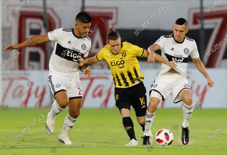 Stock Picture of Bautista Merlini (C) of Guarani vies for the ball with Jorge Recalde (L) and Diego Torres of Olimpia during their Clausura tournament final soccer match between Guarani and Olimpia at Defensores del Chaco stadium in Asuncion, Parraguay, 30 December 2020.