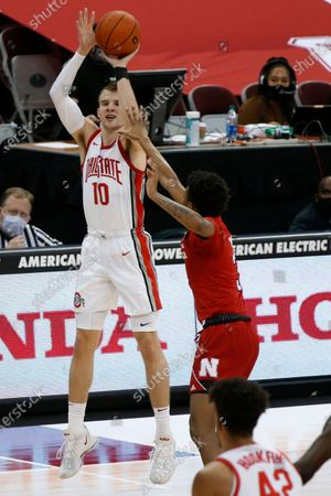 Ohio State's Justin Ahrens, left, shoots over Nebraska's Elijah Wood during the second half of an NCAA college basketball game, in Columbus, Ohio