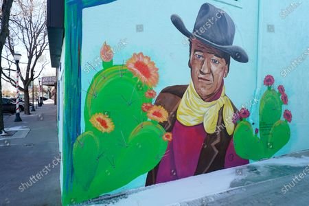 Mural of actor John Wayne graces the wall outside the Lincoln Theatre shuttered by the coronavirus on the main street, in Limon, Colo