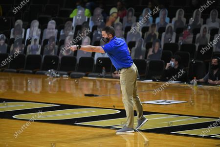 In front of cardboard cut-out fans Florida head coach Mike White motions to players during an NCAA college basketball game against Vanderbilt, in Nashville, Tenn