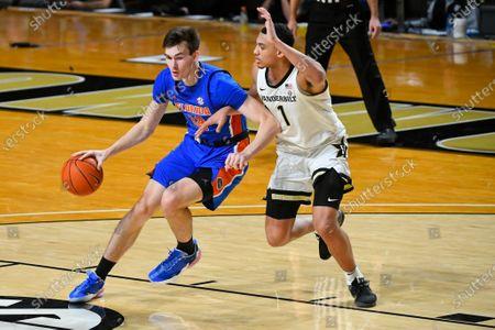 Florida forward Colin Castleton dribbles as Vanderbilt forward Dylan Disu (1) defends during an NCAA college basketball game, in Nashville, Tenn