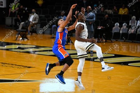 Florida guard Noah Locke is fouled by Vanderbilt guard Maxwell Evans, right, as they watch the shot during an NCAA college basketball game, in Nashville, Tenn