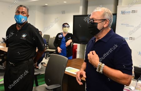 Nat Moore, 69, Miami Dolphins legend and Music producer Emilio Estefan, 67, prepare to receives their first dose of Pfizer-BioNtech COVID-19 vaccine at Jackson Memorial Hospital in Miami, Florida. Jackson Health System began Pfizer COVID-19 vaccinations for people 65 and older in Miami-Dade County.