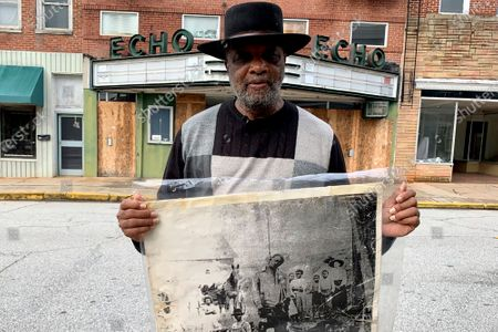 Stock Image of Rev. David Kennedy stands outside the Echo Theater holding a photo of his great uncle's lynching, in Laurens, S.C. Kennedy has fought for civil rights in South Carolina for decades