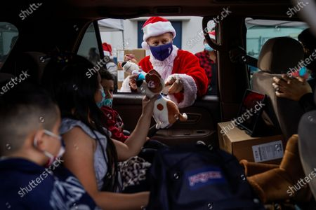 Los Angeles Unified School District Superintendent Austin Beutner, dressed as Santa Claus, gives out gifts and candy during an event at Washington Prep High School on Wednesday, Dec. 23, 2020 in Los Angeles, CA. (Kent Nishimura / Los Angeles Times)