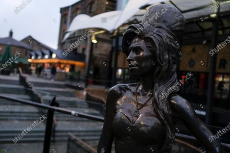 Statue of the late singer, Amy Winehouse stands in the normally busy Camden Market, in London, . The coronavirus has forced cancellation of the normal New Year party festivities as Britain's Brexit from the European bloc becomes a reality from Friday Jan. 1
