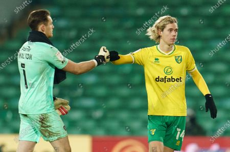 Todd Cantwell of Norwich City (14) bumps fists with Barnsley Goalkeeper Jack Walton (1)