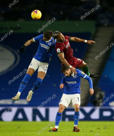 Adama Traore of Wolves uses Adam Lallana of Brighton & Hove Albion  to help him get up for a header against Ben White of Brighton & Hove Albion (L)