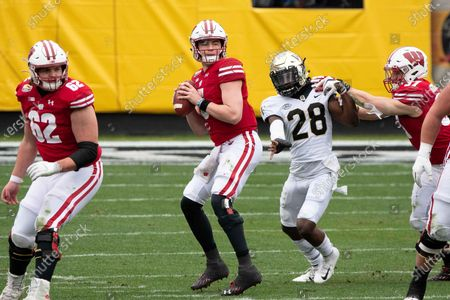 Wake Forest DB Zion Keith (28) chases down Wisconsin QB Graham Mertz (5) during the Dukeâ€s Mayo Bowl football game between the Wake Forest Demon Deacons and the Wisconsin Badgers at Bank of America Stadium in Charlotte, NC