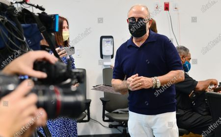 Stock Picture of Music producer Emilio Estefan, 67 and Nat Moore, 69, Miami Dolphins legend prepare to receives their first dose of Pfizer-BioNtech COVID-19 vaccine from Nadia Johnson, RN from Jackson Health System, at Jackson Memorial Hospital-Christine E. Lynn Rehabilitation Center on December 30, 2020 in Miami, Florida. Jackson Health System began Pfizer COVID-19 vaccinations for people 65 and older in Miami-Dade County.