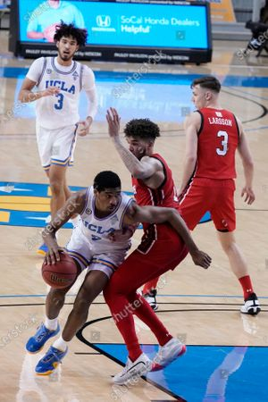 Guard Chris Smith, left, is defended by Utah forward Timmy Allen during the second half of an NCAA college basketball game, in Los Angeles