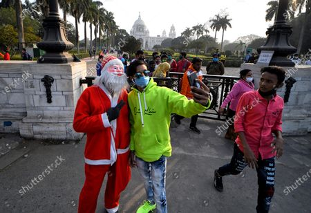 Visitors seen taking selfies with Santa Clause outside of Victoria Memorial Hall. Victoria Memorial inscribed as a World Heritage Site by UNESCO built in 1906 to 1921 in memory of Queen Victoria the Empress of India.