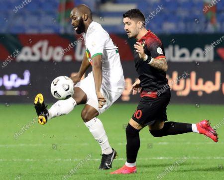 Al-Ettifaq's player Souleymane Doukara (L) in action against Al-Wehda's Dimitri Petratos (R) during the Saudi Professional League soccer match between Al-Ettifaq and Al-Wehda at Prince Mohammed Bin Fahd Stadium, in Dammam, Saudi Arabia, 01 January 2021.