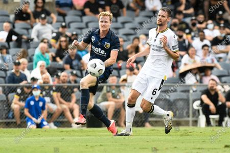 Matthew Simon of Central Coast Mariners watches his cross as Aleksandar Jovanovic of Macarthur FC closes in; Campbelltown Stadium, Leumeah, New South Wales, Australia; A League Football, Macarthur FC versus Central Coast Mariners.